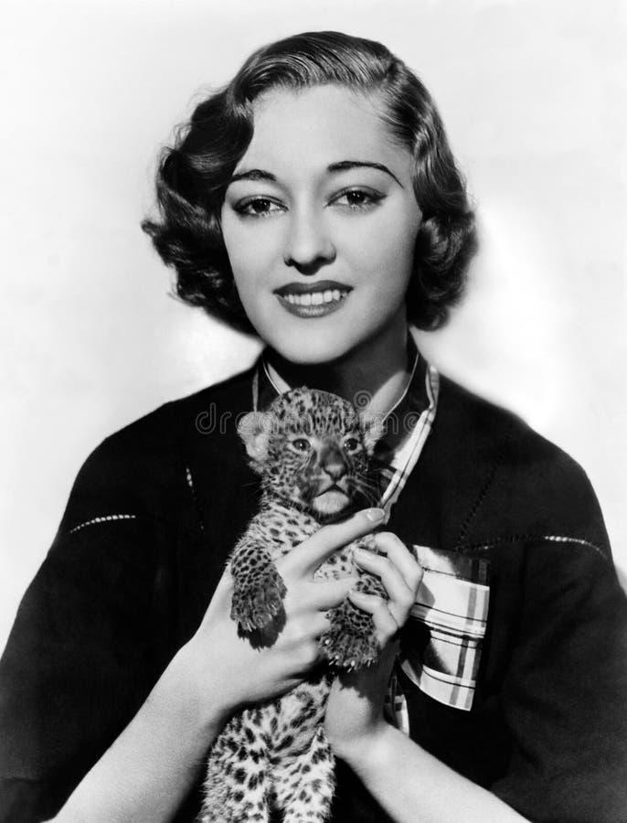 Mujer que sostiene el cachorro minúsculo del leopardo (todas las personas representadas no son vivas más largo y ningún estado ex fotos de archivo libres de regalías