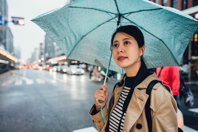 Mujer que sostiene el paraguas azul y que camina en lluvia fotos de archivo