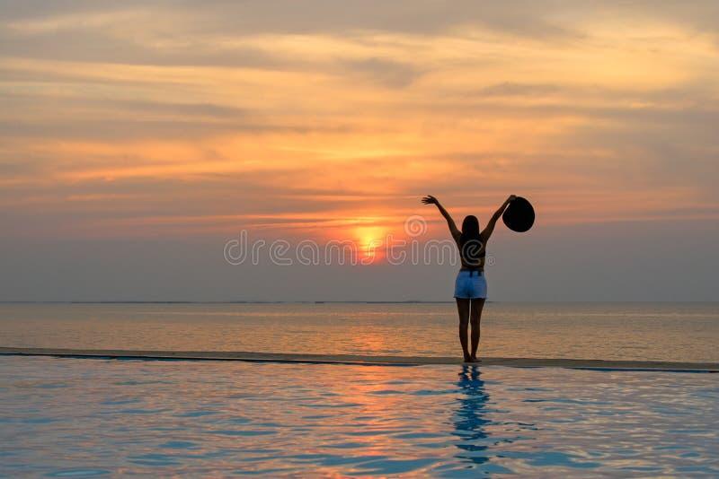Mujer que sostiene el sombrero que se relaja en la piscina en la puesta del sol foto de archivo