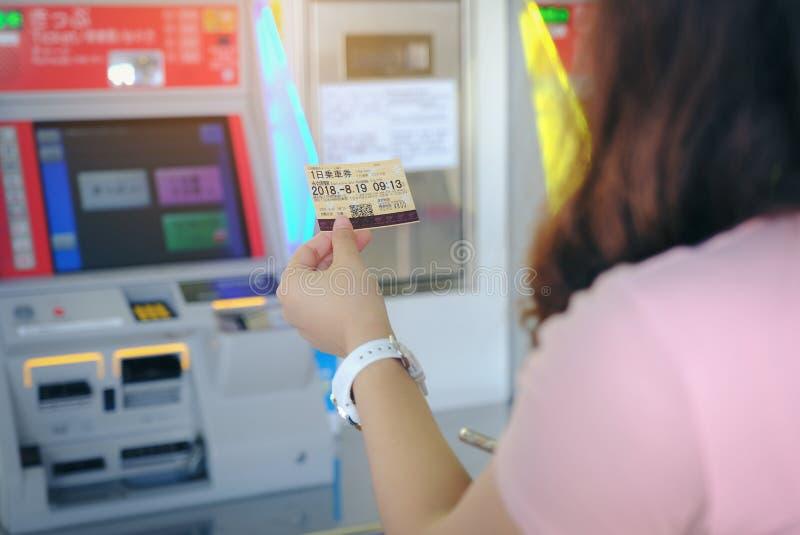 Mujer que sostiene el subterráneo un boleto de día a la estación de Okinawa en v auto foto de archivo libre de regalías