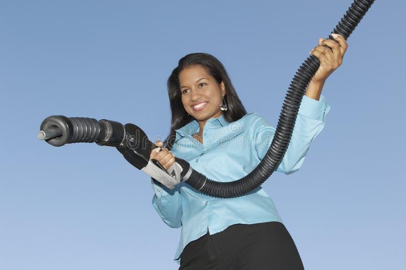 Mujer que sostiene el surtidor de gasolina fotografía de archivo