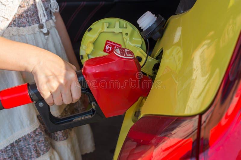 Mujer que sostiene el surtidor de gasolina imagenes de archivo