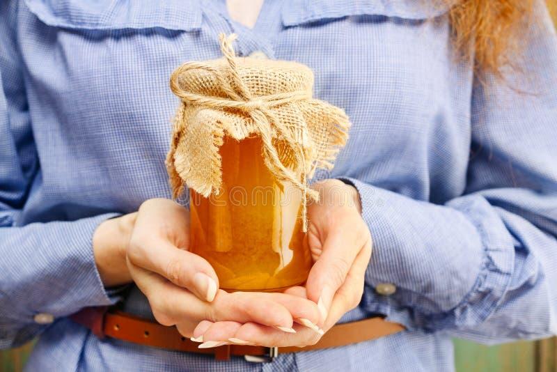 Mujer que sostiene el tarro de cristal de miel fotos de archivo