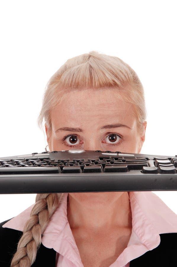 Mujer que sostiene el teclado sobre su cara fotos de archivo