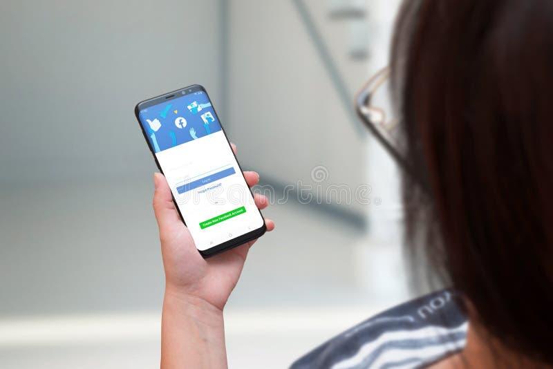 Mujer que sostiene el teléfono elegante con una nueva versión reajustada de Facebook imágenes de archivo libres de regalías