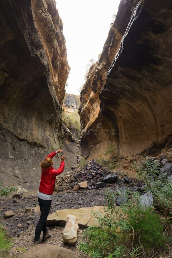 Mujer que sostiene el teléfono elegante y que toma la foto en el acantilado escénico dentro del barranco en contraluz Atracción t fotos de archivo libres de regalías