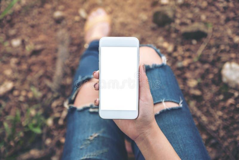 Mujer que sostiene el teléfono móvil blanco con la pantalla de escritorio en blanco mientras que se sienta en la tierra al aire l imágenes de archivo libres de regalías