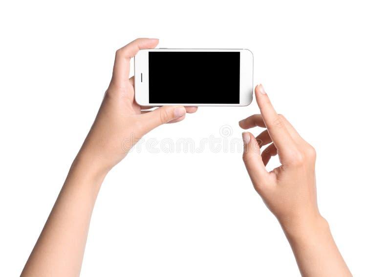 Mujer que sostiene el teléfono móvil con la pantalla en blanco en manos en el fondo blanco imágenes de archivo libres de regalías