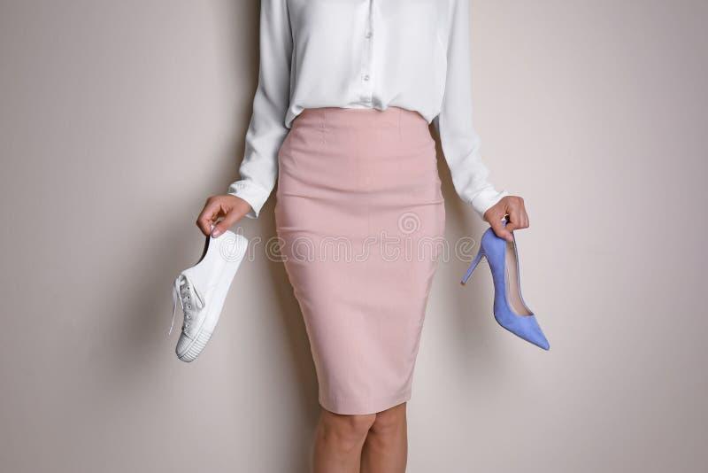 Mujer que sostiene el zapato de tacón alto y la zapatilla de deporte imagen de archivo libre de regalías
