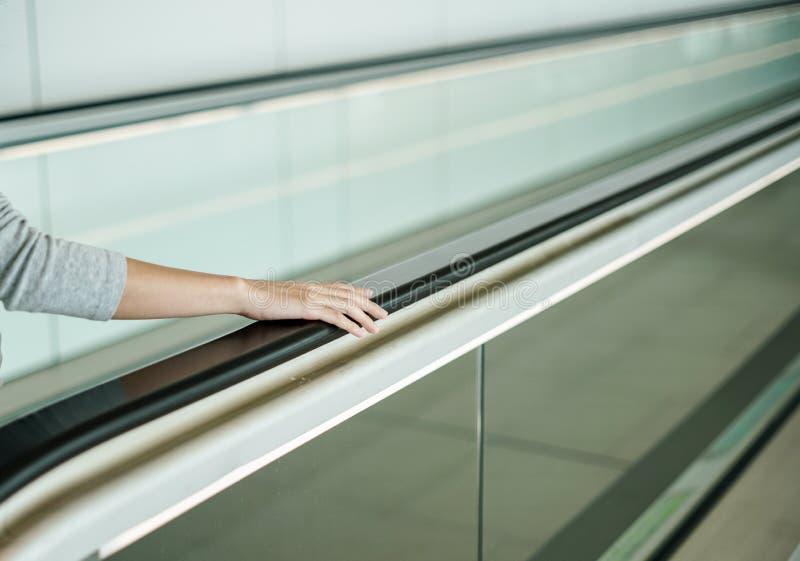 Mujer que sostiene encendido la barandilla cuando escalera móvil ascendente fotos de archivo