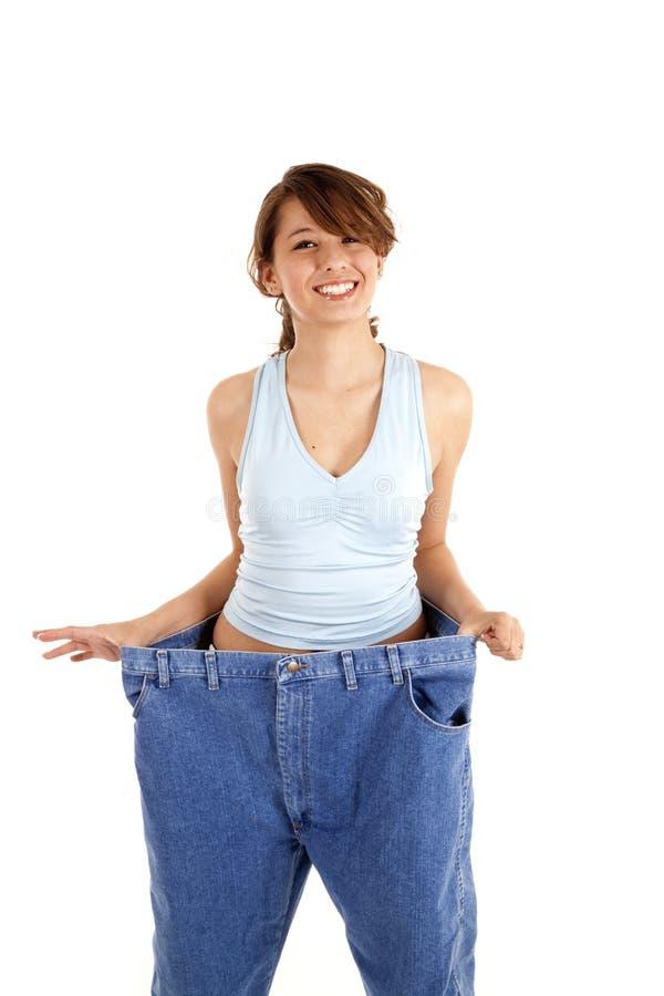 Mujer que sostiene hacia fuera los pantalones grandes fotografía de archivo