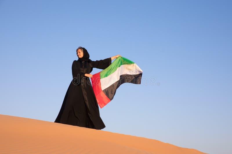 Mujer que sostiene la bandera de United Arab Emirates en el desierto imagenes de archivo