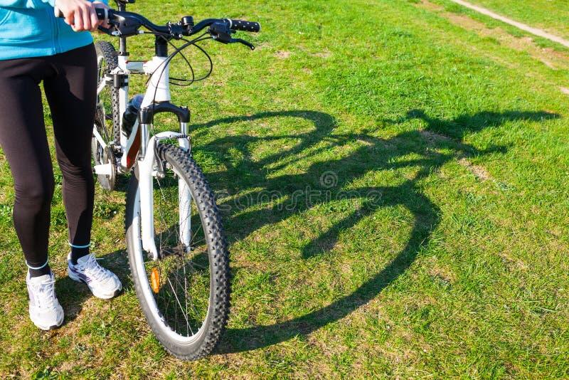 Mujer que sostiene la bici foto de archivo libre de regalías