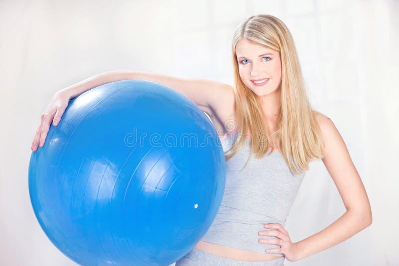 Mujer que sostiene la bola azul de los pilates fotos de archivo