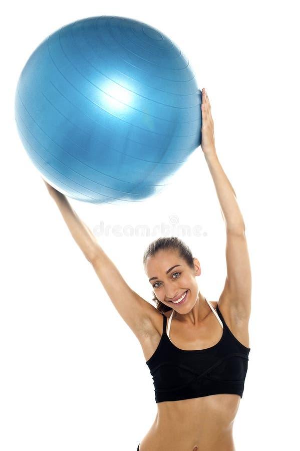 Mujer que sostiene la bola azul grande de los pilates sobre su cabeza fotos de archivo