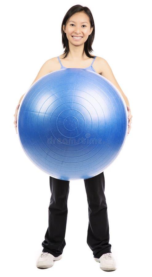 Mujer que sostiene la bola de los pilates fotos de archivo