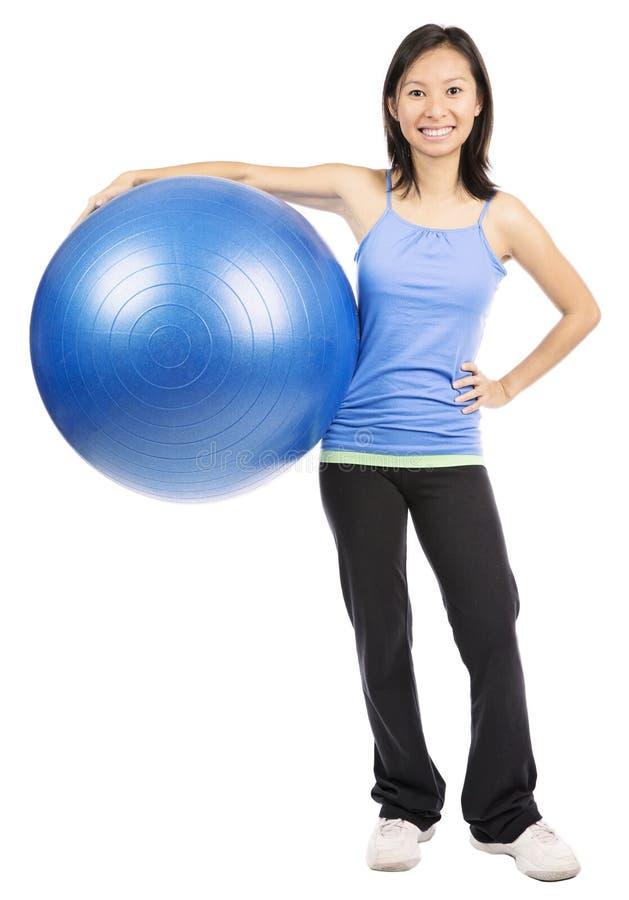 Mujer que sostiene la bola de los pilates fotografía de archivo