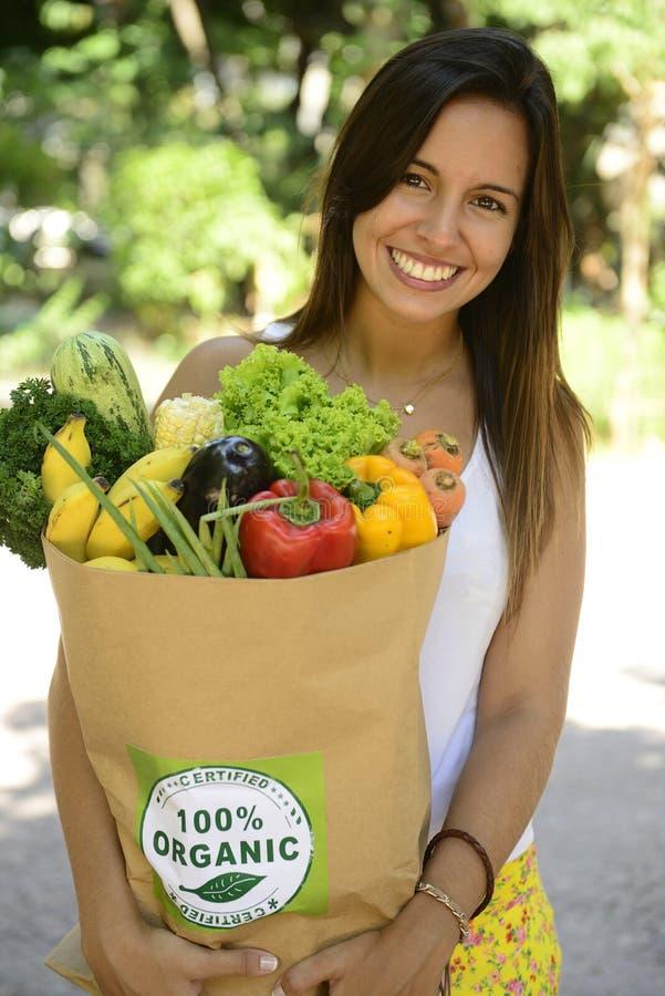 Mujer que sostiene la bolsa de papel que hace compras con las verduras y las frutas orgánicas o bio. imagen de archivo