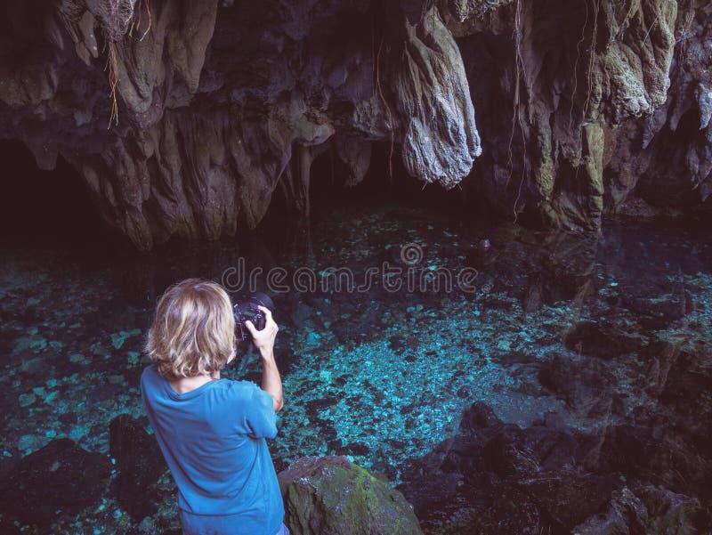 Mujer que sostiene la cámara del dlsr que fotografía el lago natural dentro de la cueva Reflexión colorida, agua transparente de  imagen de archivo