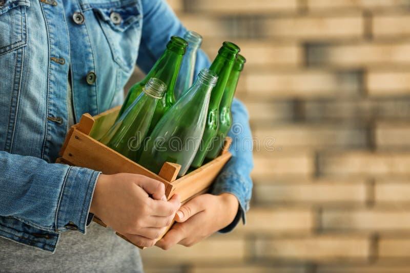 Mujer que sostiene la caja de madera con las botellas de cristal vacías cerca de la pared de ladrillo imágenes de archivo libres de regalías