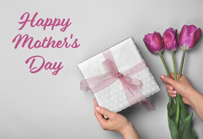 Mujer que sostiene la caja y los tulipanes elegantes de regalo para el día de madre en fondo ligero foto de archivo
