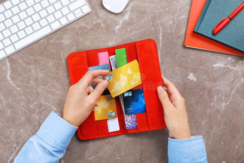 Mujer que sostiene la cartera roja con las tarjetas de crédito foto de archivo libre de regalías