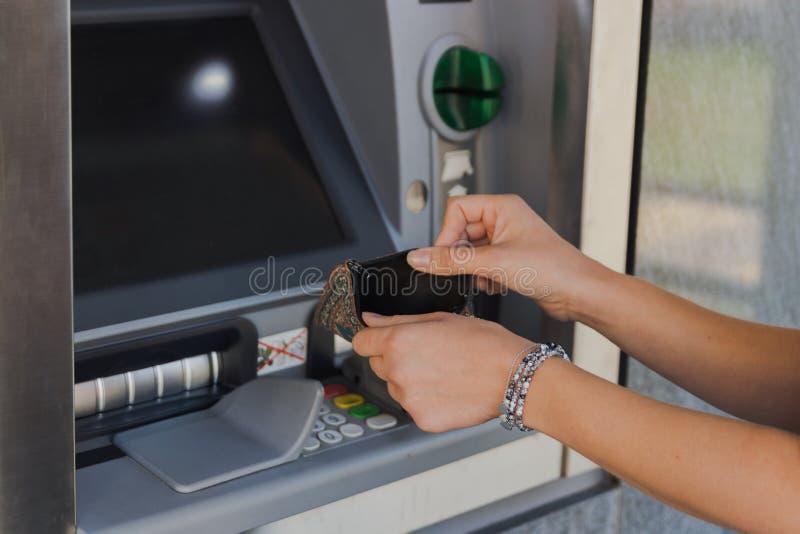 Mujer que sostiene la cartera vacía cerca de la máquina del cajero automático El concepto de ser se rompi? fotografía de archivo libre de regalías