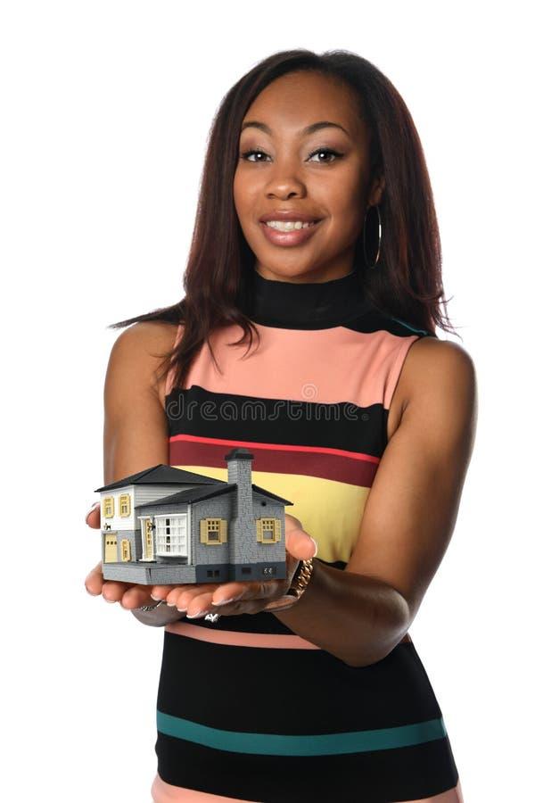 Mujer que sostiene la casa miniatura fotografía de archivo libre de regalías