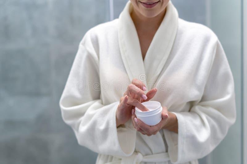 Mujer que sostiene la crema en las manos, colocándose en el cuarto de baño imagen de archivo libre de regalías