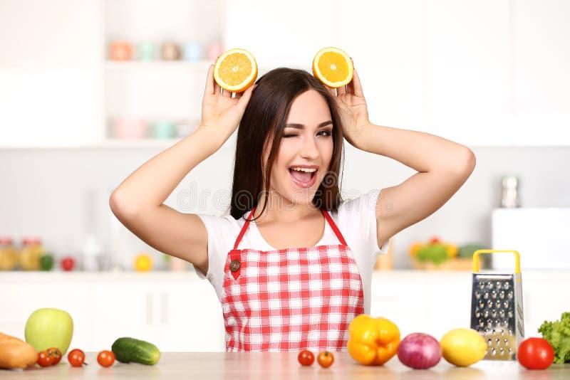 Mujer que sostiene la fruta anaranjada cortada fotos de archivo