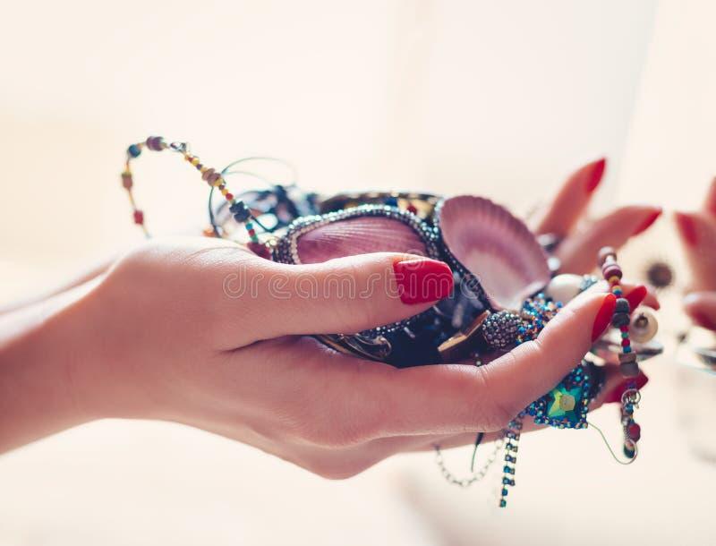 Mujer que sostiene la joyería delante del espejo foto de archivo