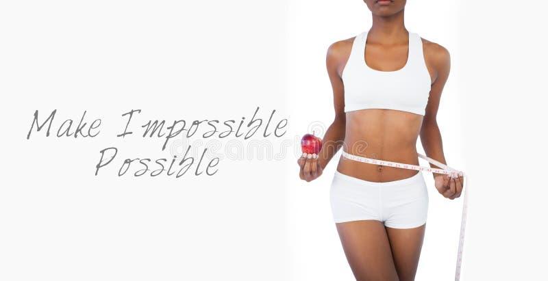 Mujer que sostiene la manzana y que mide su cintura fotografía de archivo