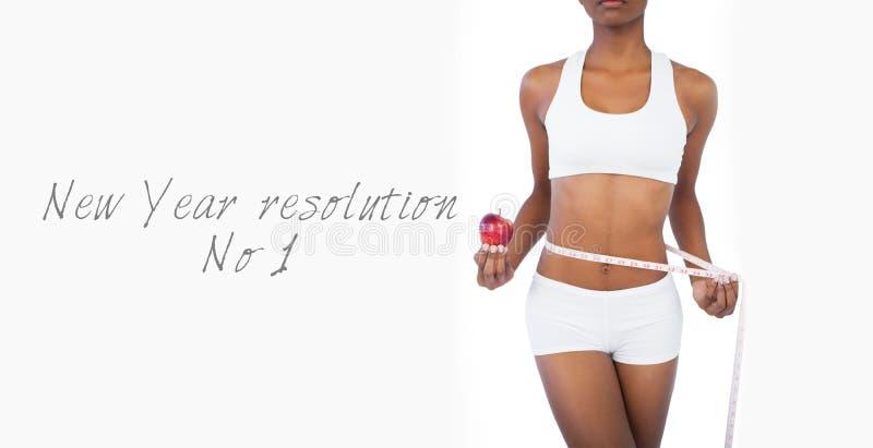 Mujer que sostiene la manzana y que mide su cintura imagen de archivo
