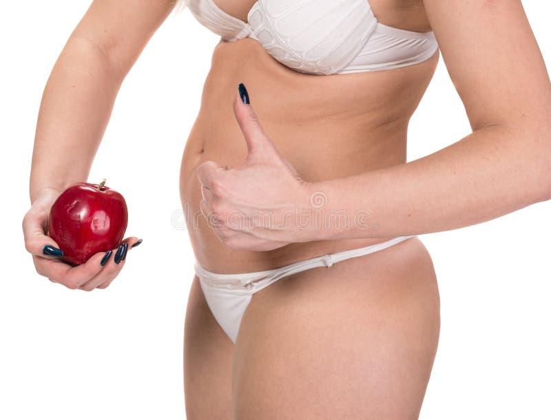 Mujer que sostiene la manzana y que muestra la muestra aceptable imagenes de archivo