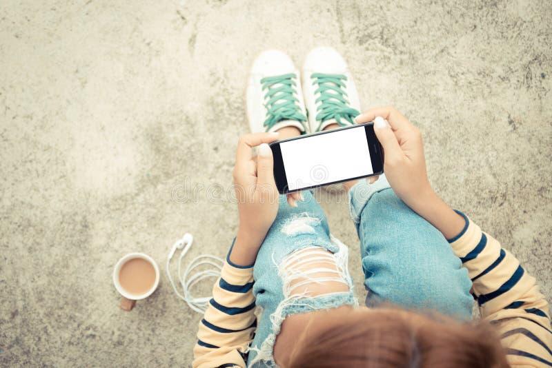 Mujer que sostiene la pantalla blanca del teléfono en estilo del vintage de la visión superior foto de archivo libre de regalías