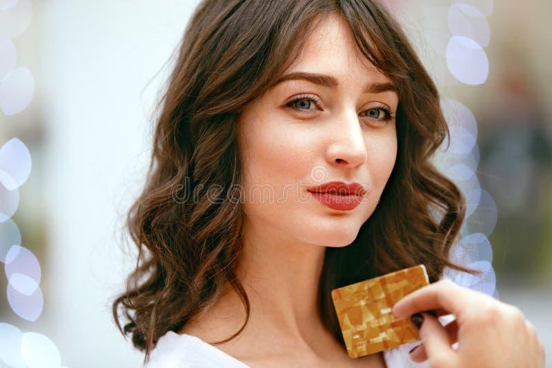 Mujer que sostiene la tarjeta de crédito en alameda de compras imagen de archivo libre de regalías
