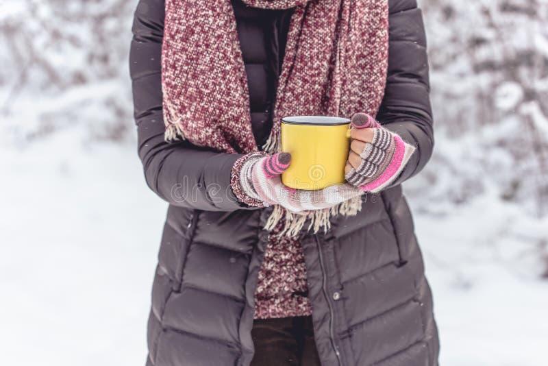 Mujer que sostiene la taza amarilla de bebida caliente al aire libre fotos de archivo libres de regalías