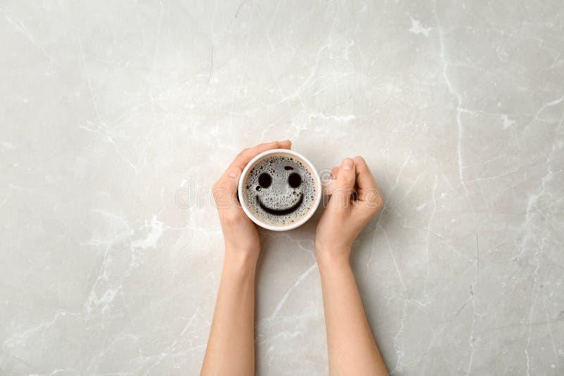 Mujer que sostiene la taza de café caliente delicioso con espuma y de sonrisa en el fondo ligero, visión superior Mañana feliz, b fotos de archivo