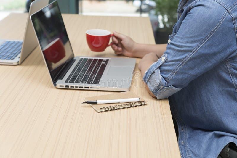 mujer que sostiene la taza de café con el ordenador portátil, el cuaderno y la pluma fotos de archivo libres de regalías