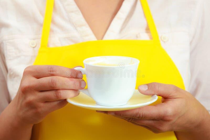 Mujer que sostiene la taza de café en cocina imágenes de archivo libres de regalías