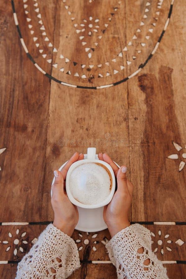 Mujer que sostiene la taza de café en la tabla de madera, visión superior imagen de archivo libre de regalías