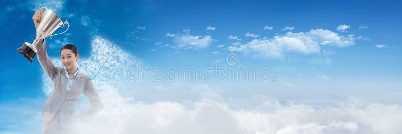 Mujer que sostiene la taza del trofeo en la celebración en la transición de la nube del cielo imagenes de archivo