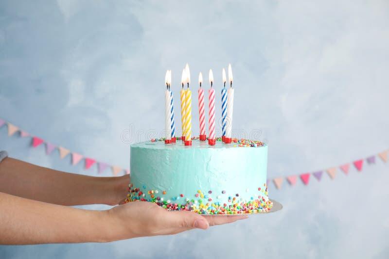 Mujer que sostiene la torta de cumpleaños deliciosa fresca con las velas fotografía de archivo