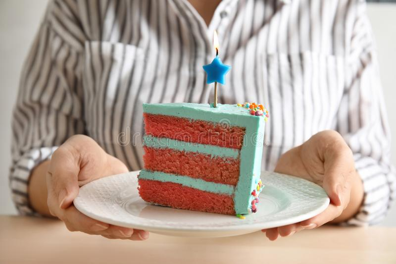 Mujer que sostiene la torta de cumpleaños deliciosa fresca con la vela imagen de archivo libre de regalías
