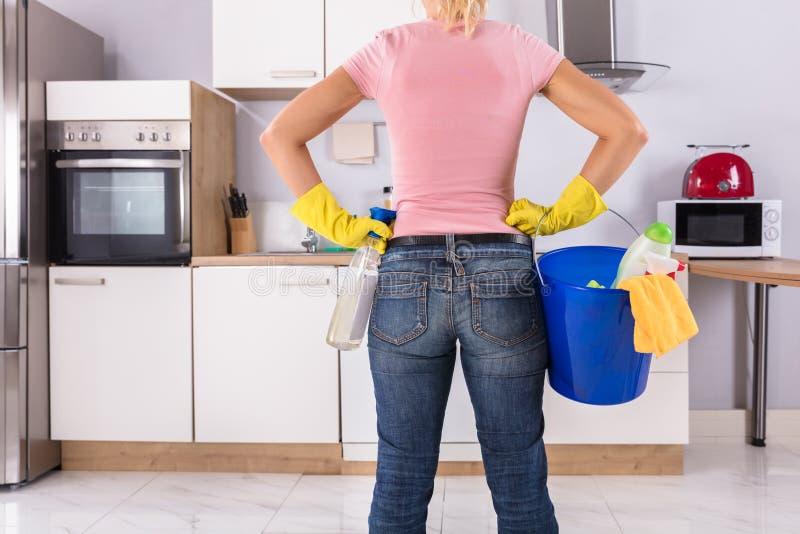 Mujer que sostiene las herramientas y los productos de la limpieza imagen de archivo libre de regalías