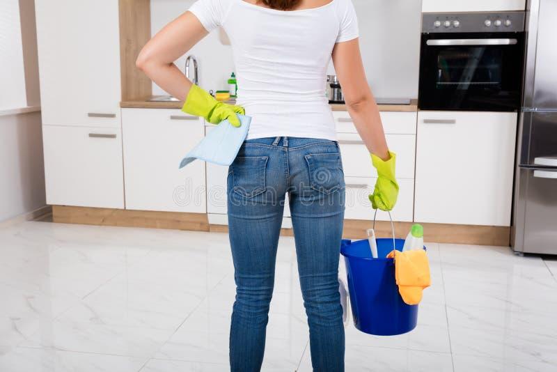 Mujer que sostiene las herramientas y los productos de la limpieza en cubo imagen de archivo
