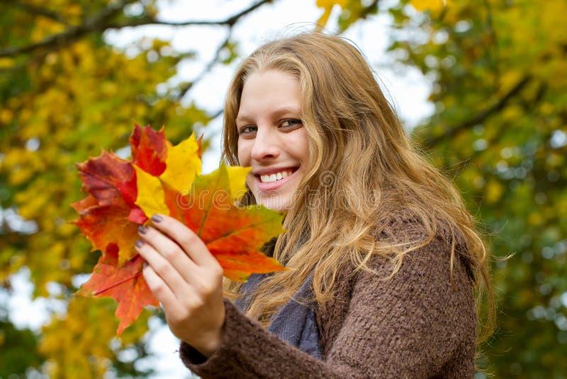 Mujer que sostiene las hojas de otoño fotografía de archivo libre de regalías