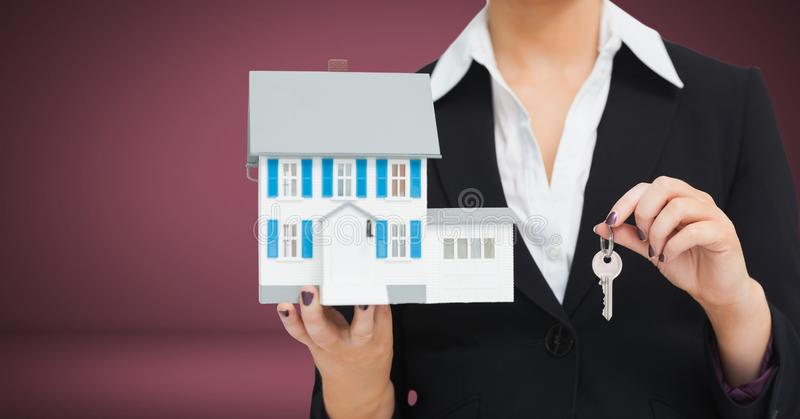 Mujer que sostiene llave y la casa delante de la ilustración foto de archivo
