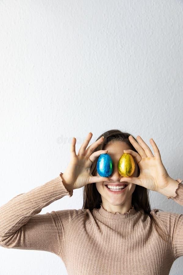 Mujer que sostiene los huevos de Pascua azules y de oro del chocolate delante de sus ojos fotos de archivo