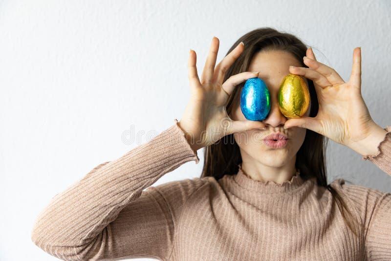 Mujer que sostiene los huevos de Pascua azules y de oro del chocolate delante de sus ojos foto de archivo